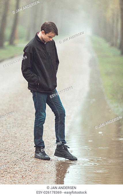 Single male teenager looking sad with hands in pockets and dipping foot in puddle along side forest road