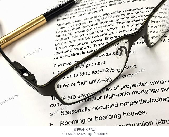 Eye glass and pen on document as background