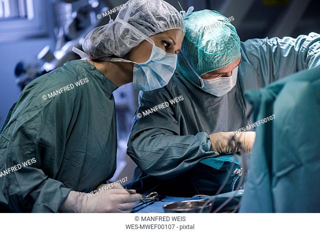 Neurosurgeon with nurse closing operation wound