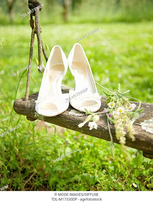 A pair of white wedding shoes on a wooden swing
