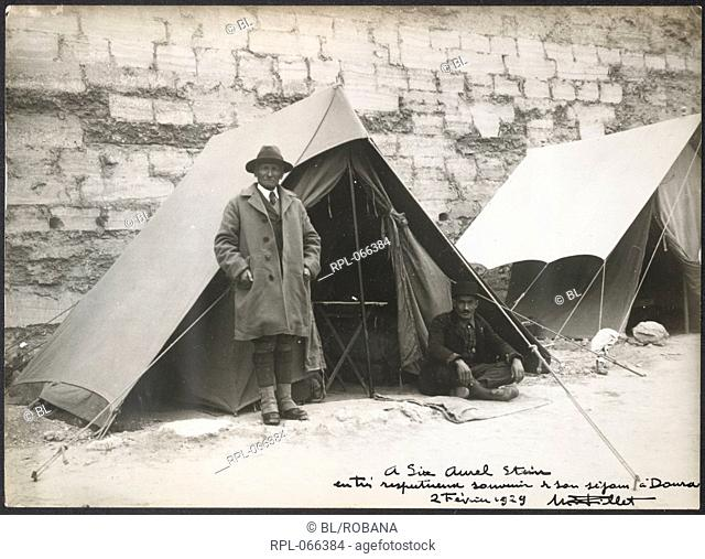 Full-length portrait of Sir Aurel Stein, standing in front of his tent pitched in front of a wall. Originally published/produced in February 1929 Illustrated by...