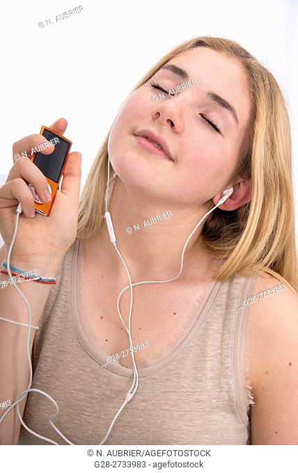 Portrait of happy blond teenage girl holding her i-pod in one hand and listening to music, with eyes closed, at home