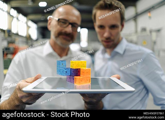 Two men examining workpiece on tablet in a factory