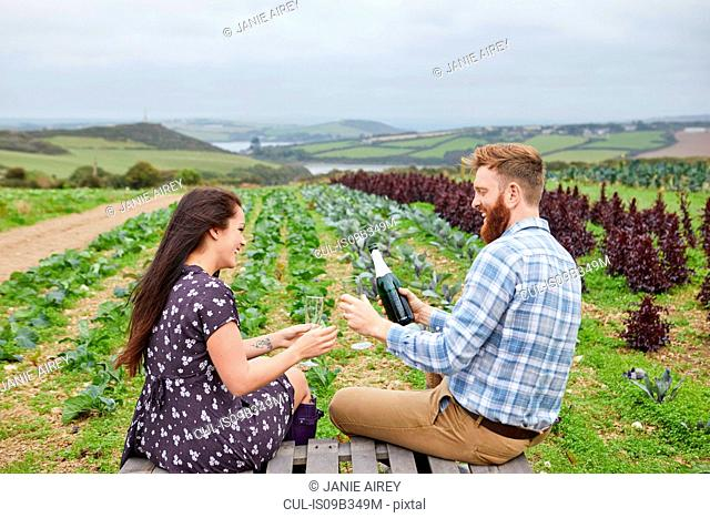 Couple in rural location sitting on pallets pouring champagne