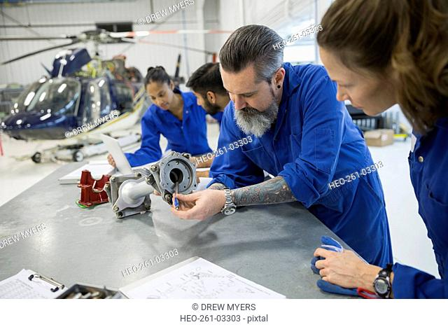 Helicopter mechanics examining cog part in airplane hangar