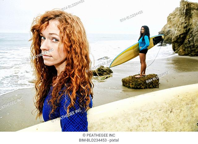 Serious women holding surfboards at beach
