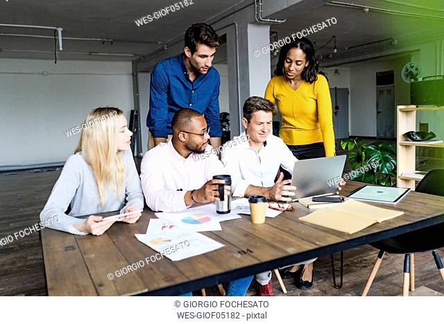 Confident business team having a meeting in loft office looking at laptop together