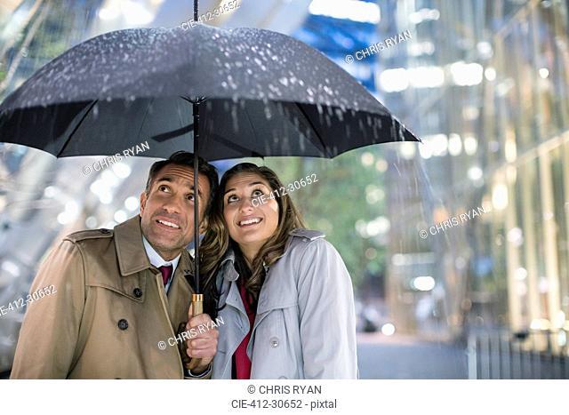 Businessman and businesswoman watching rain under umbrella