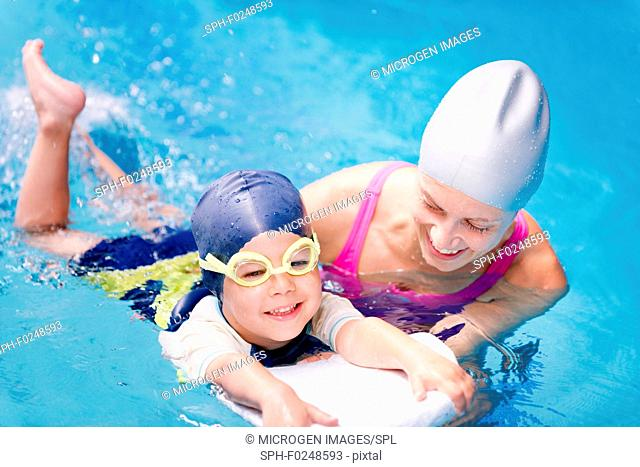 Little boy learning to swim with swimming instructor