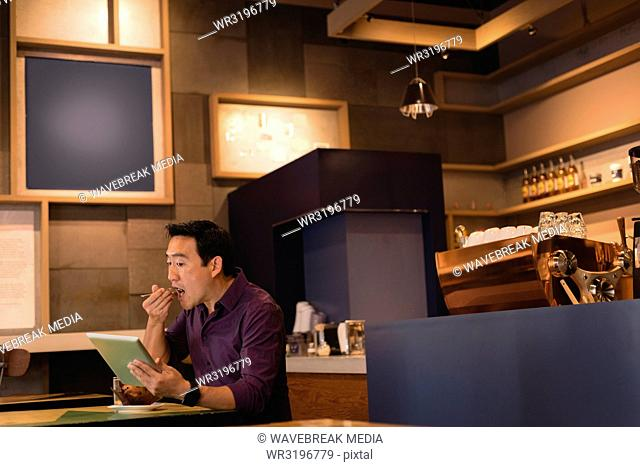 Man using digital tablet in coffee shop