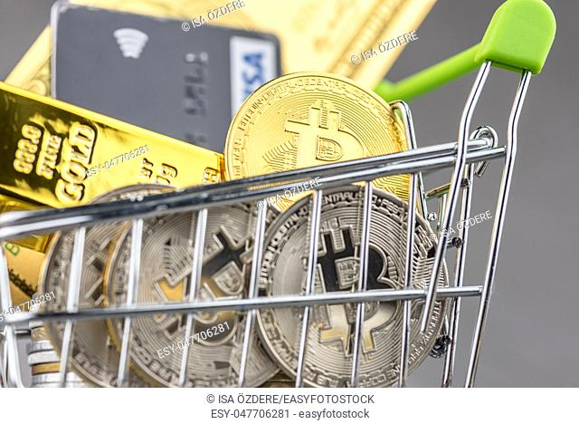 View of metal bitcoins and VISA credit cards and American dollar banknotes in shopping trolley. Concept image for cryptocurrency