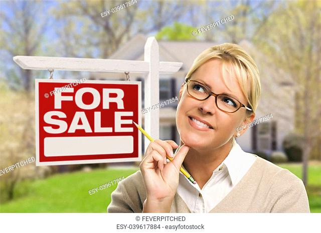 Attractive Young Adult Woman with Pencil in Front of For Sale Real Estate Sign and House