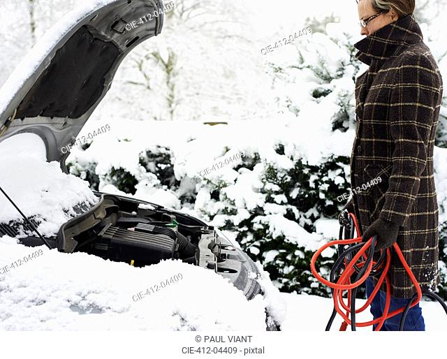 Woman working on broken down car in snow