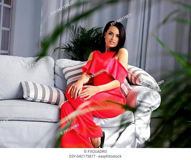 A brunette female dressed in a red evening dress sits on a coach in a room with green plants and grey interior