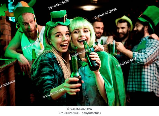 Two girls in a wig and a cap are photographed in a bar. They celebrate St. Patrick's Day. They are having fun