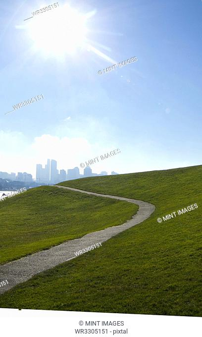 Sun shining over paved road on grassy hillside, Seattle, Washington, United States