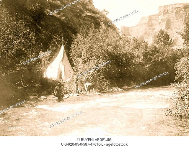 Crow man with two children and woman at river's edge, tipi, surrounded by trees and mountains