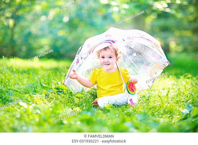 Happy laughing baby girl playing under a colorful umbrella in a