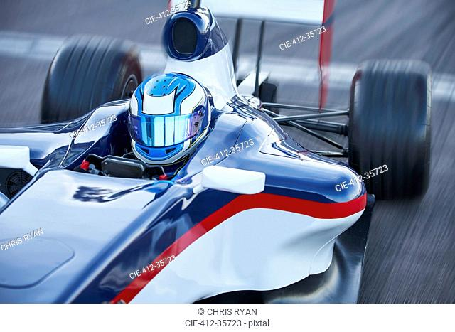 Formula one race car driver in helmet on sports track