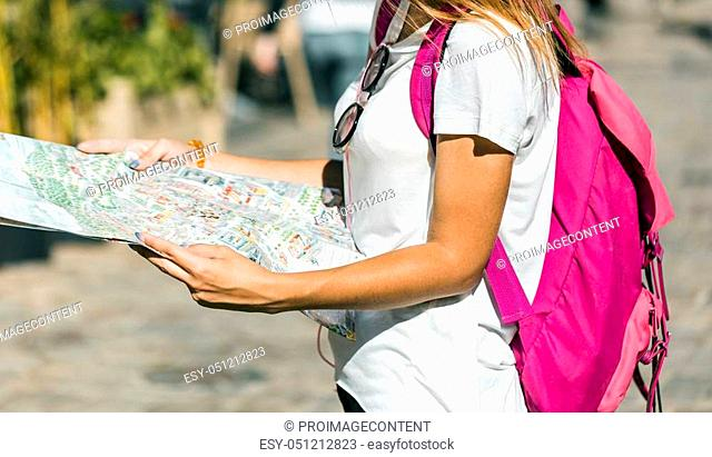 Pretty caucasian tourist girl is looking at the map in the old city center location, sunny day