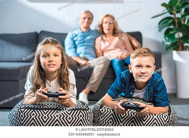 focused children playing video game with joysticks white grandparents sitting behind