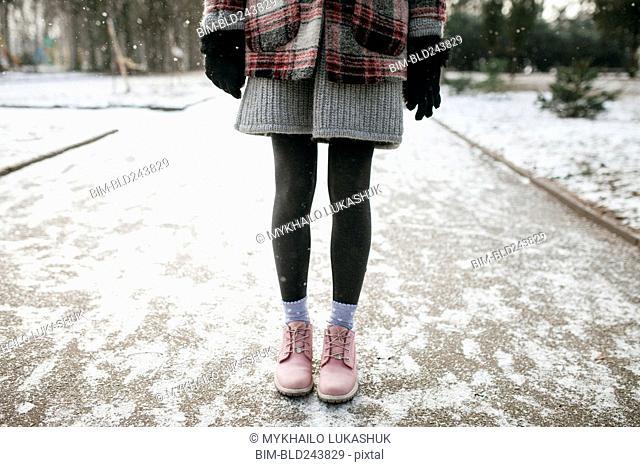 Legs of Caucasian woman standing in snow