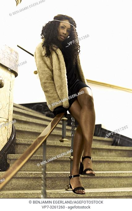 woman sitting on handrail at stairs, in Munich, Germany