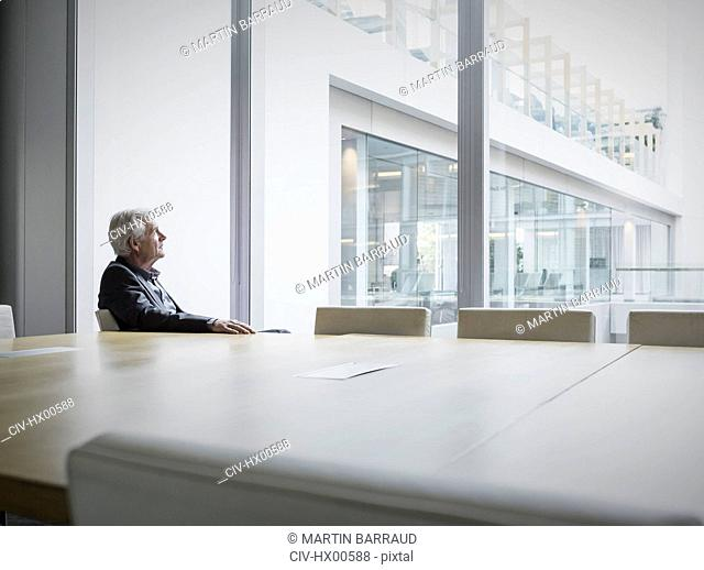 Pensive senior businessman looking out conference room window