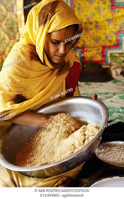 Woman preparing couscous, Chinguetti. Adrar Plateau, Sahara Desert, Mauritania