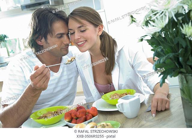 man feeding woman