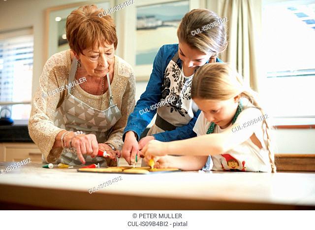Senior woman and granddaughters decorating Christmas tree cookies