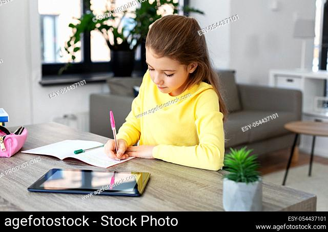student girl writing to notebook at home