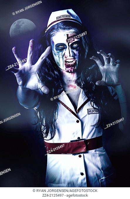 Female medical zombie biting at the lip in chilling bloodthirsty style standing at a night cemetery in the cool mist and moonlight. Dawn of the dead