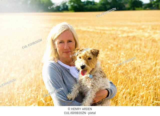 Mature woman standing in field, holding pet dog