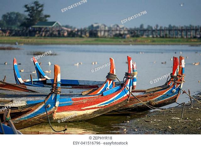 group of traditional boat in Taungthaman Lake near the U Bein Bridge, famous landmark and tourist attraction of Amarapura Township, Mandalay, Myanmar (Burma)