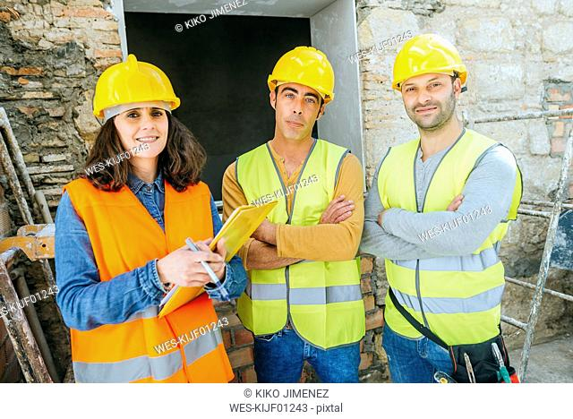 Woman with two construction workers on construction site