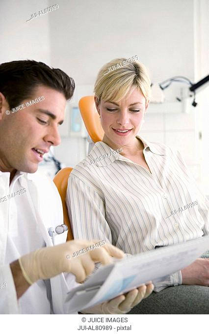 Male dentist talking to female patient