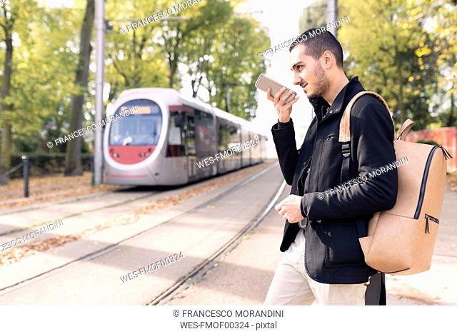 Young man with cell phone at tram stop outdoors