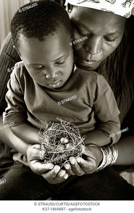 Black mother with child looking at nest with egg