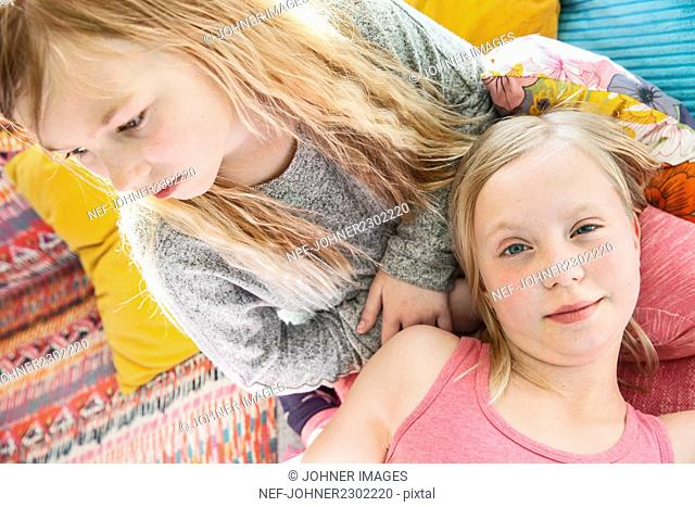 Smiling sisters on sofa