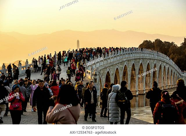 Tourists over the 17 Arch Bridge at sunset, The Summer Palace; Beijing, China