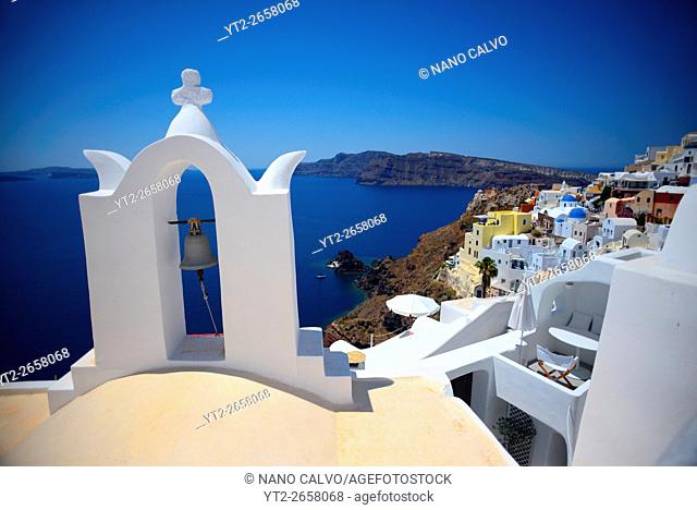Church bell and hillside buildings in Oia, Santorini, Greek Islands, Greece