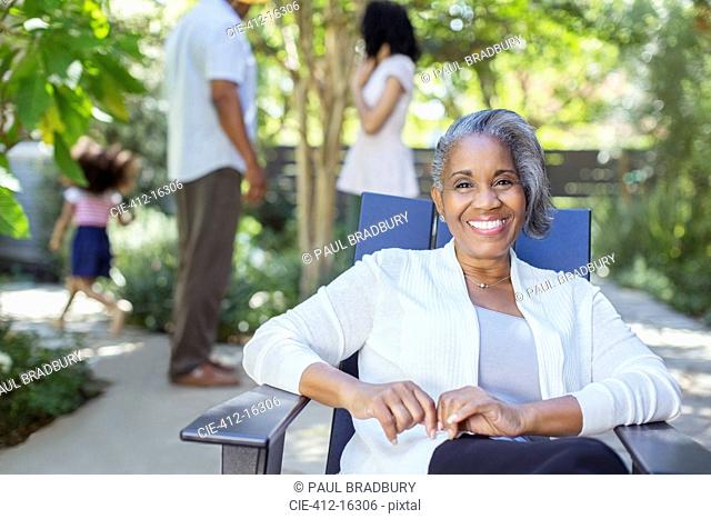 Portrait of smiling senior woman on patio with family in background