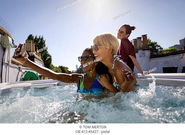 Young women friends taking selfie in sunny rooftop hot tub