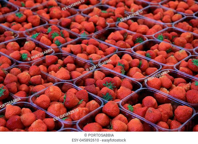 Strawberries in small plastic containers on a market stall