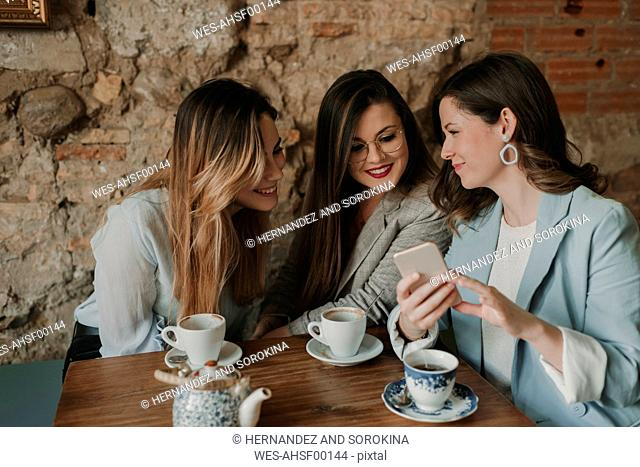 Three young women looking at cell phone in a cafe