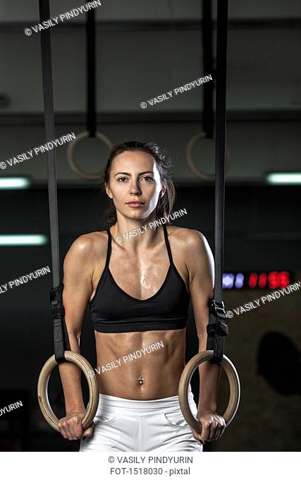 Portrait of young woman exercising on gymnastic rings at gym