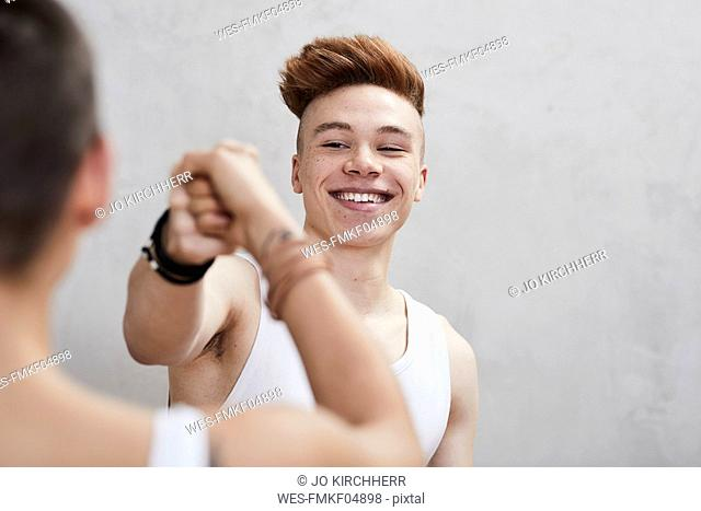 Portrait of smiling young man doing fist bump with girlfriend