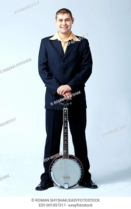 Man in dark suit standing with banjo, full length