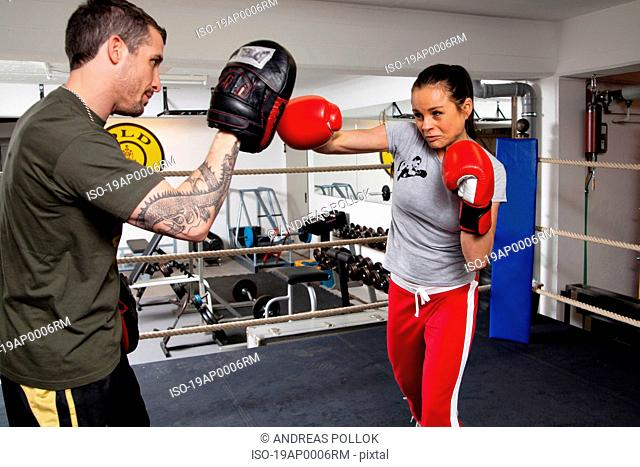 Young woman with coach in boxing ring